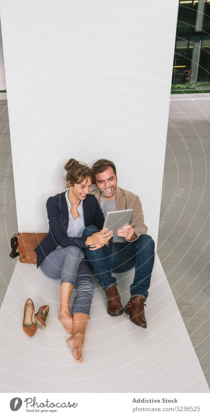 Businesspeople hugging and using tablet on street businesspeople couple social media building sit rest city together man woman manager entrepreneur casual relax