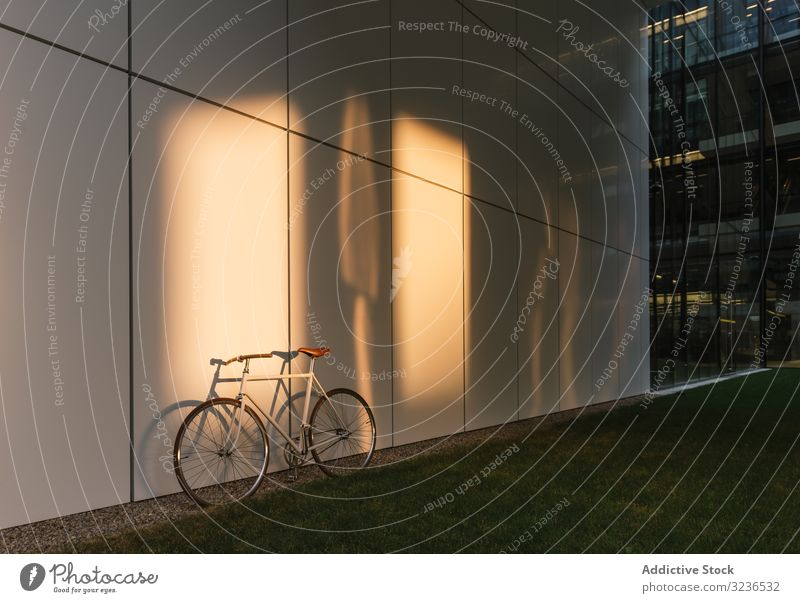 Bicycle parked outside modern building bicycle street city sidewalk urban transport exterior contemporary downtown commute structure construction pavement path
