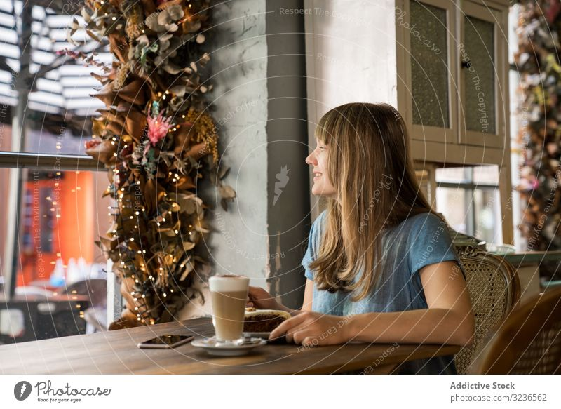 Cheerful woman using a phone in cafe smartphone coffee lifestyle young mobile female happy cheerful smile laugh leisure drink casual restaurant sitting hold