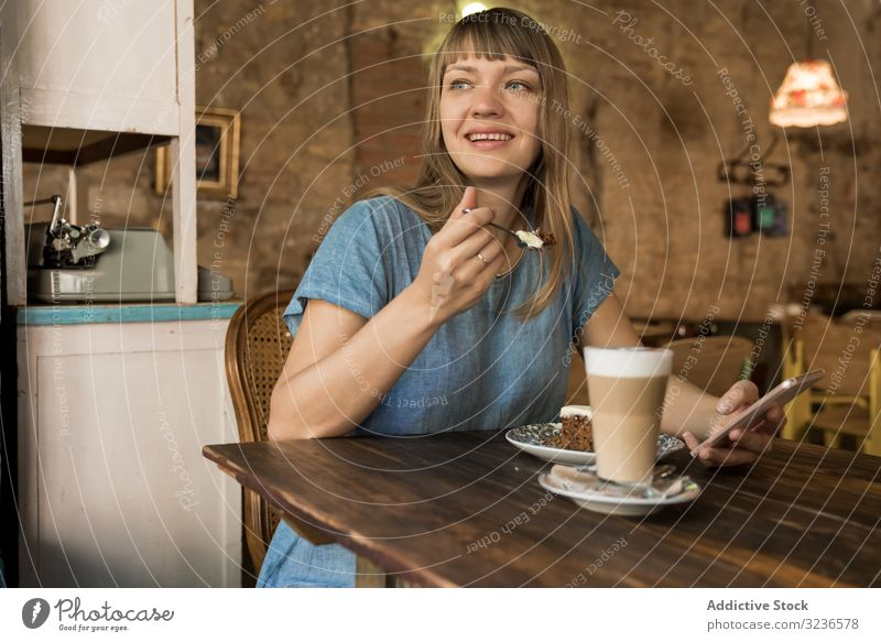 Woman holding spoon with slice of cake woman cafe piece coffee lifestyle young happy female tasty cheerful leisure drink casual try restaurant sitting break