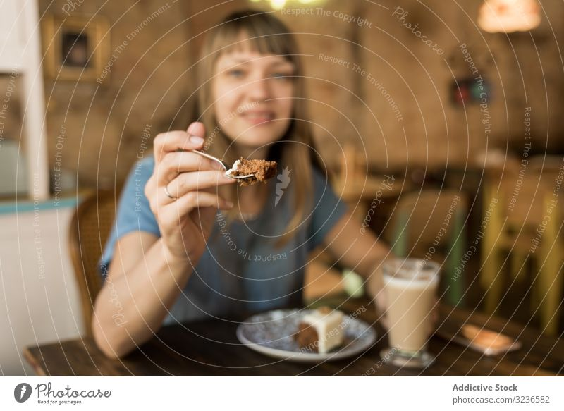 Woman holding spoon with slice of cake woman cafe giving piece coffee lifestyle young happy offer female tasty cheerful leisure drink casual try restaurant