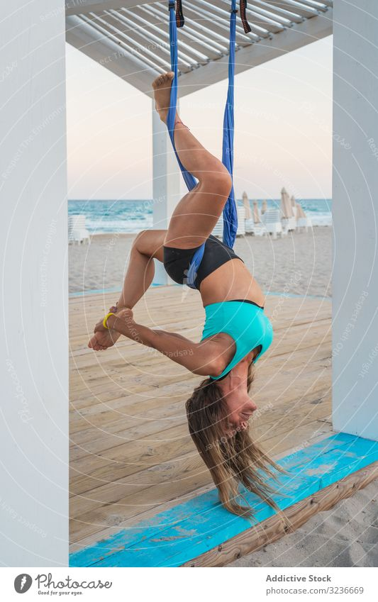 Relaxed woman performing aerial yoga hanging head down and touching leg hanging down exercise balance acrobatic fitness anti-gravity yoga young posture training