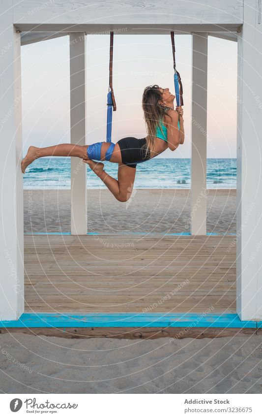 Cheerful woman stretching leg on blue hammock for aerial yoga on wooden stage exercise balance acrobatic fitness anti-gravity yoga young posture training sport