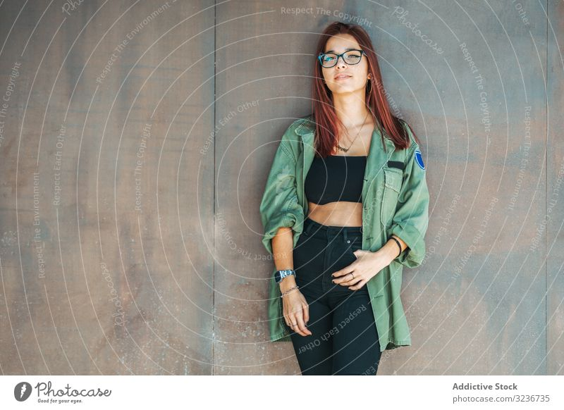 Stylish confident bright woman in glasses leaning on wall and looking at camera stylish smart provocative hairstyle clever attractive female cute beauty pretty