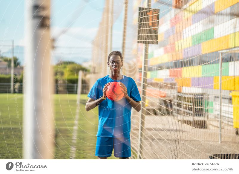 Black teenager on football field net training sportswear ethnic grass male adolescent soccer lawn sunny daytime black african american competition workout game