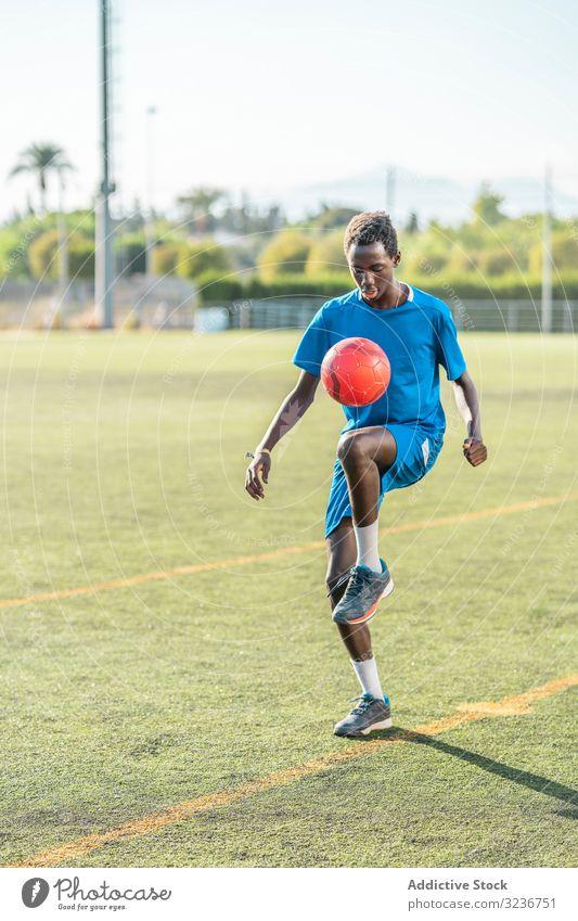 Ethnic teenager juggling football ball juggle field training player sportswear ethnic grass male adolescent knee soccer lawn sunny daytime black