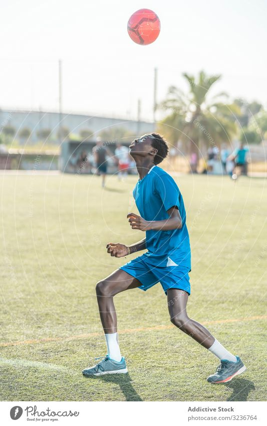 Skinny black teenager jugging football ball on head juggle field training player sportswear ethnic grass male adolescent soccer lawn sunny daytime