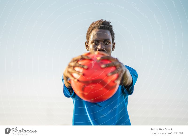 African American football player with ball teenager outstretched arms sky cloudless training sportswear ethnic show male adolescent soccer lawn black