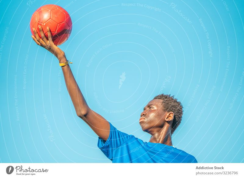 Black teenager with football ball against sky raised arm cloudless training sportswear ethnic holding show male adolescent soccer lawn black african american