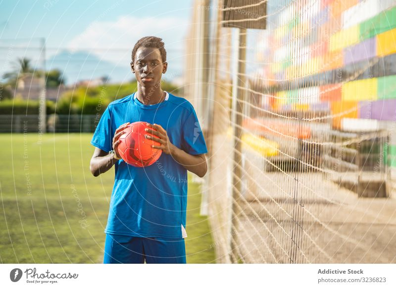 Black teenager on football field lean net training sportswear ethnic grass male adolescent soccer lawn sunny daytime black african american competition workout