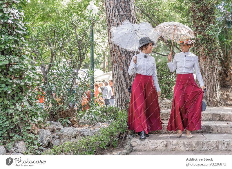 Vintage women walking in park together talk vintage step dress parasol smile costume female summer event retro old fashioned umbrella cheerful happy friend