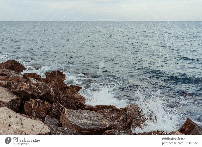 Sea waves hitting rocky cliff sea coast stone water foam splash seashore ocean nature seascape coastline landscape beach weather scenic dark power spray crash
