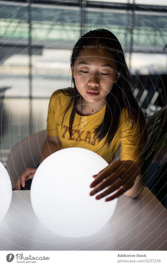 Asian woman examining round lamps on table light creative excitement hall illuminated female interior asian art design electrical power light bulb