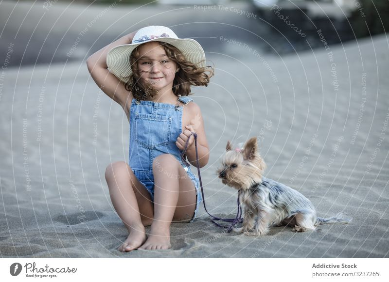 Cute girl holding hat and sitting on beach with dog pet sand summer sea animal friendship companion vacation fun shore nature windy together travel cute terrier