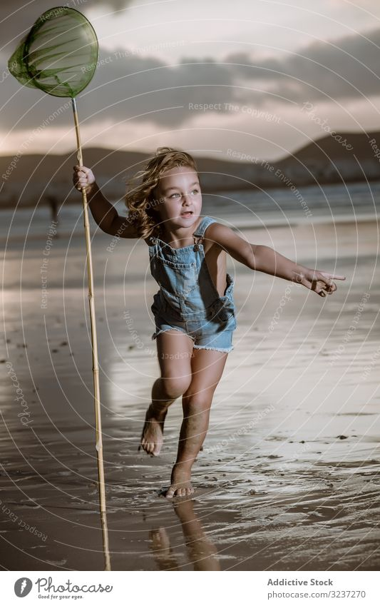 Curios kid with butterfly net walking barefoot on wet shore seaside cute childhood nature catch activity little natural coast beach vacation holiday resort sand