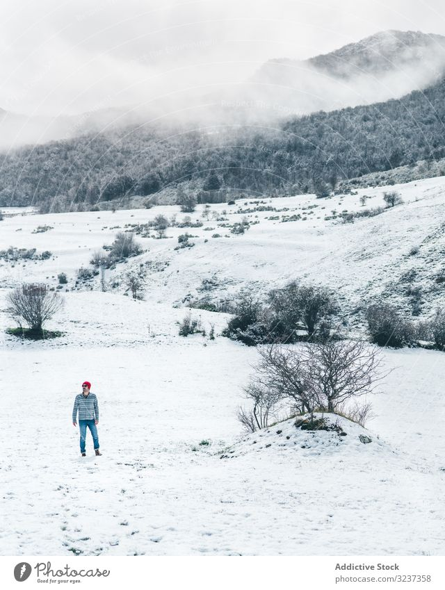 Man walking on winter field man snow relaxation enjoy country forest recreation alone meadow hill tree frozen quiet calm tranquil cold nature valley journey
