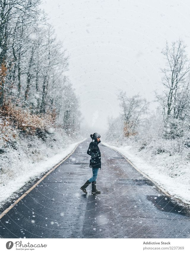 Young woman crossing winter country road snow foggy cloudy gloomy forest walk young alone lonely tree frozen cold female nature relaxation journey activity