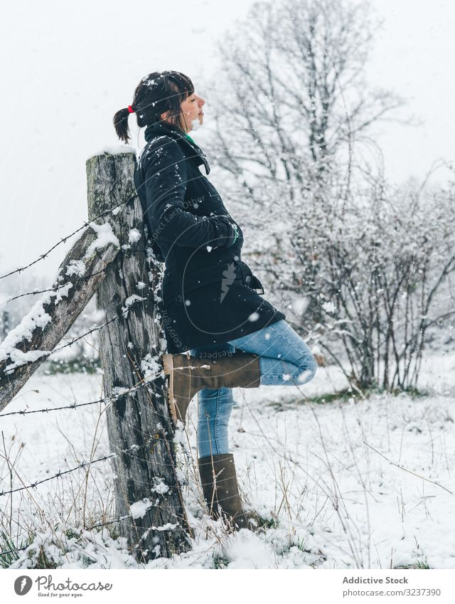 Young woman enjoying snow day on countryside field relaxation calm winter forest recreation foggy cloudy gloomy young alone female leaning thoughtful dreaming