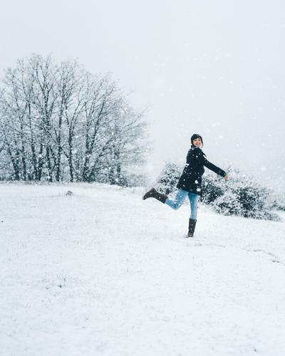 Woman playing with snow on winter field woman relaxation enjoy country forest recreation alone meadow hill tree frozen quiet jumping calm tranquil cold nature