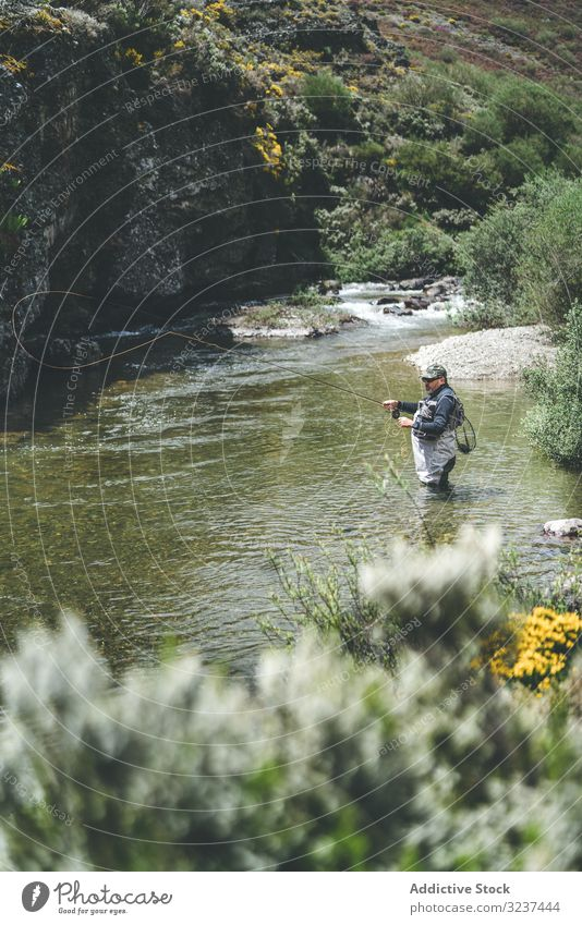 Confident man fishing with rod while standing in river stream confident equipment harling wader mountain torrent cliff forest greenery adult water fisherman