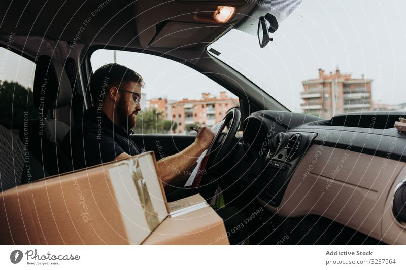 Courier preparing cartons for express delivery man courier write box pensive check marker street prepare order service attentive job distribution package male