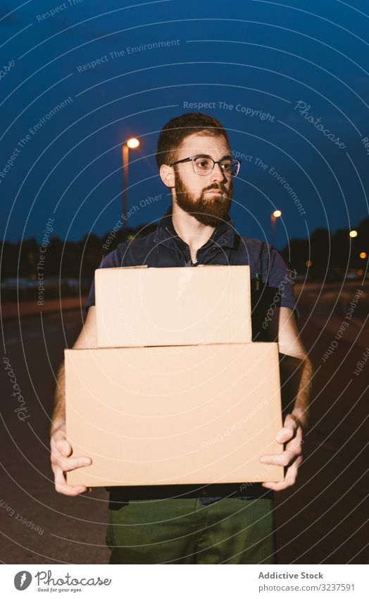 Courier delivering cardboard boxes in evening delivery courier shopping man service order pensive destination package distribution client carry customer carton