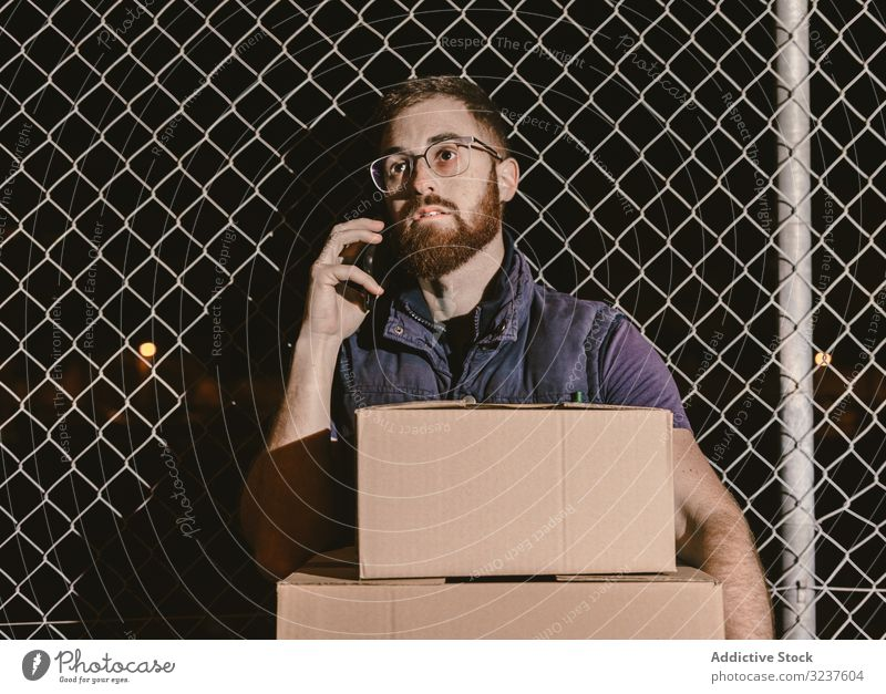 Courier with carton waiting client on street in evening man box courier delivery shipment service destination distribution order express package male