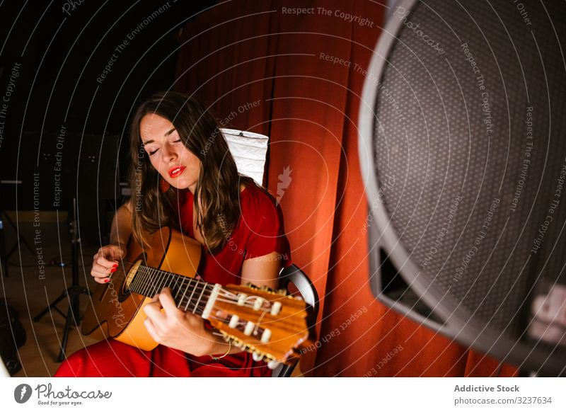 Creative woman singing and playing guitar on stage performance music musician singer guitarist concert performer entertainment sound artist instrument player