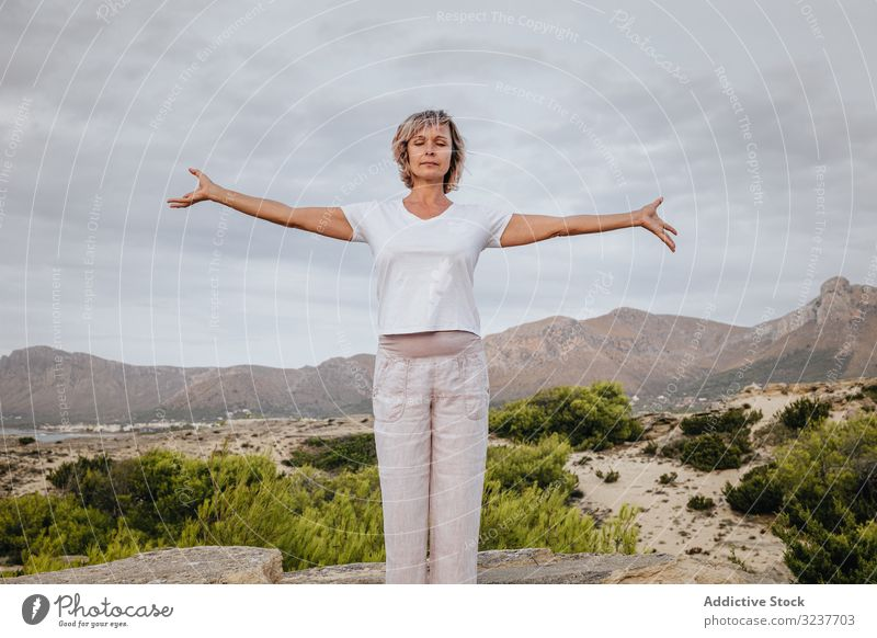 Barefoot woman meditating on stone meditation exercise rock tai chi closed eyes nature sky cloudy training female adult barefoot breath healthy fit yoga