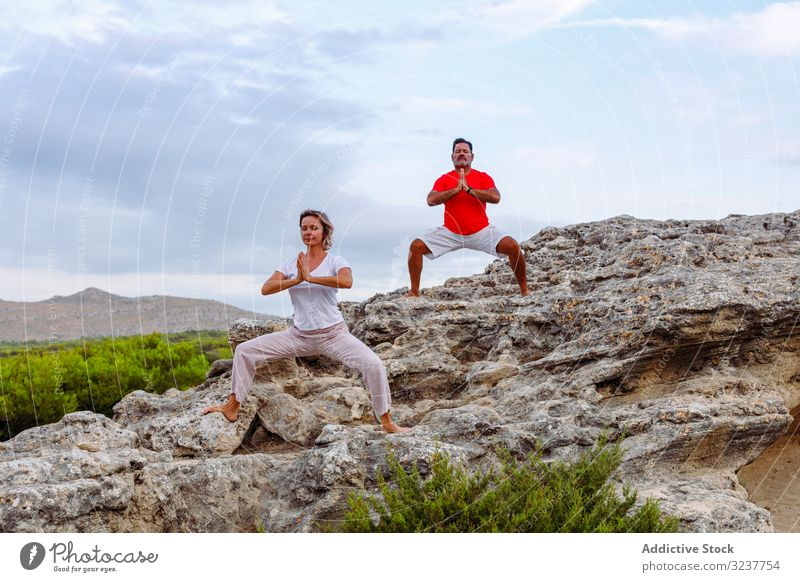 Couple meditating on rock couple meditation breath exercise tai chi clasped hands closed eyes nature sky cloudy training woman adult healthy fit yoga