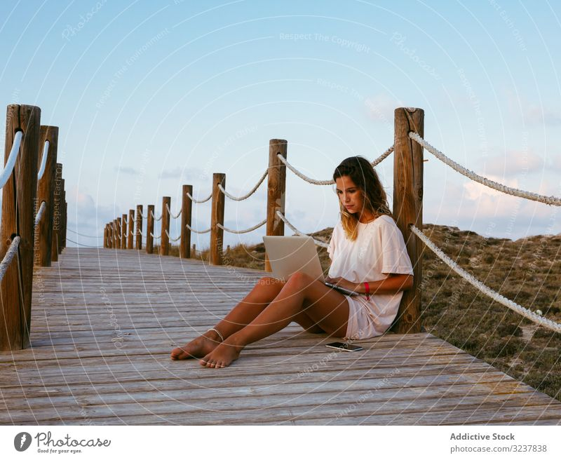 Smart resting woman remote worker using laptop while lying on bridge freelancer browsing computer young female working nature devises gadgets vacation travel
