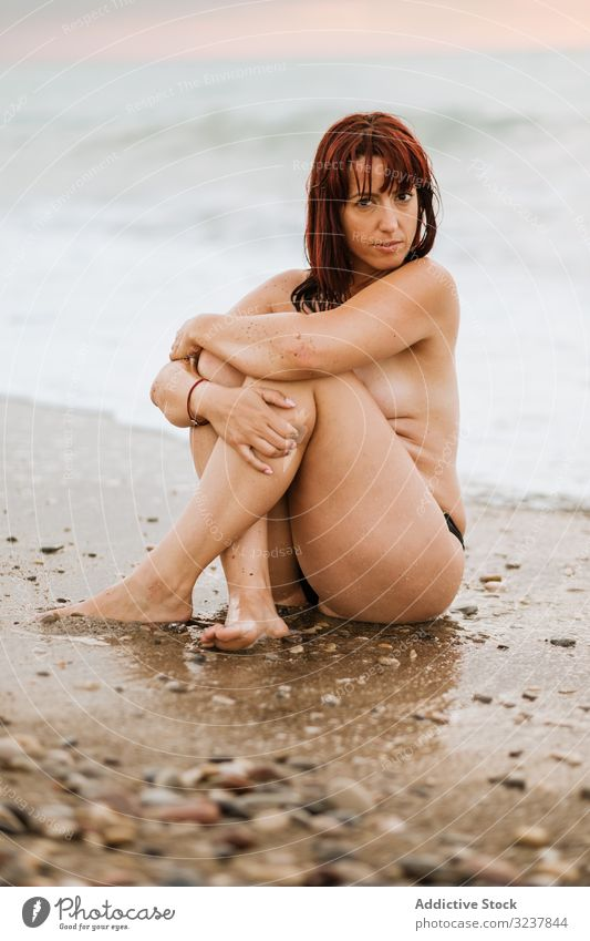 Naked woman sitting near sea waves naked nude erotic sexy sensual free seductive topless elegance breast body skin unclothed uncovered figure bare female nudist