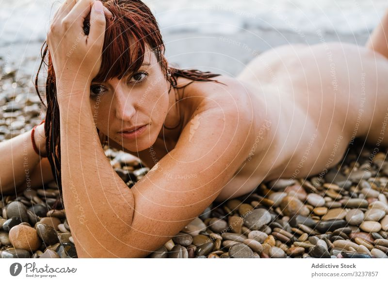 Naked woman lying down near sea waves naked nude erotic sexy sensual free seductive topless elegance breast body skin unclothed uncovered figure bare female