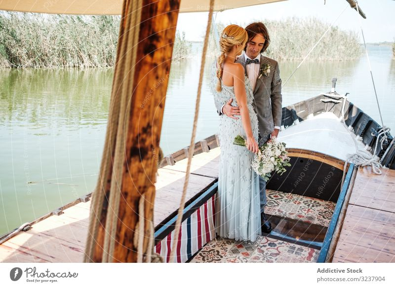 Couple holding hands while on boat groom bride wedding marriage love celebration couple wife woman happiness cheerful embracing hugging relationship newlywed