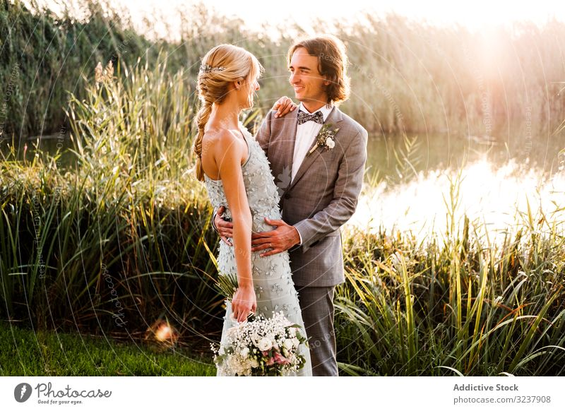 Happy newly wedded couple delighting in event at nature groom bride wedding marriage love celebration wife woman happiness kissing plants green pond mere