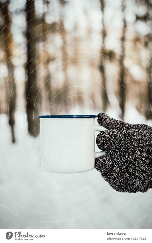 Man's hand in knitted glove holding white enamel cup Seasons Cold Common cold Gloves Knitted Nature Fresh Morning Wood Forest Exterior shot Vertical Selective
