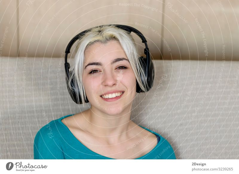 Close up of a smiling young woman with headphones while sitting on sofa and looking camera Lifestyle Happy Beautiful Face Relaxation Leisure and hobbies