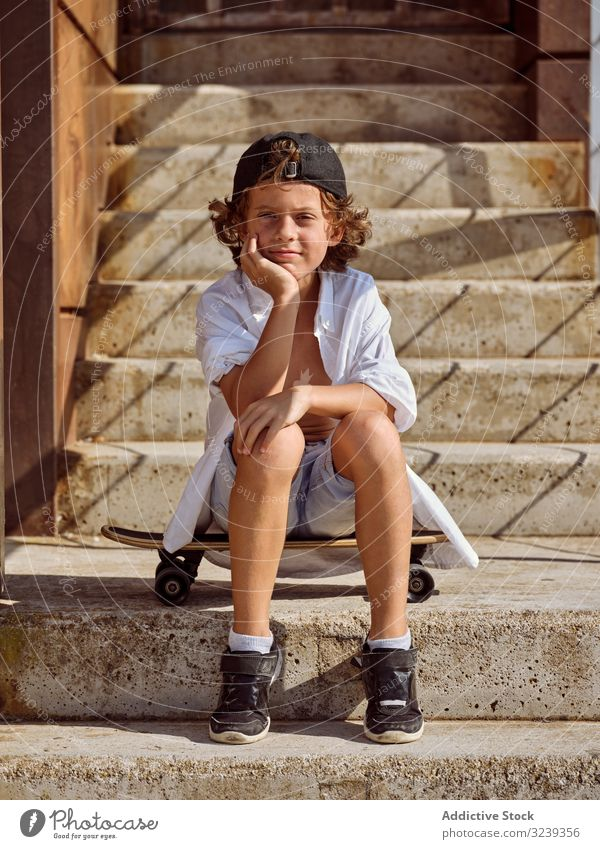 Child sitting on stairs in skatepark boy skateboard style cheerful happy child lifestyle rest leaning on hand sport leisure hobby young childhood summer sunny