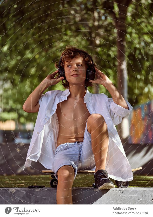 Boy with headphones relaxing in skatepark child lifestyle pensive cool interest beginner dream sport leisure hobby boy young childhood summer sunny active urban