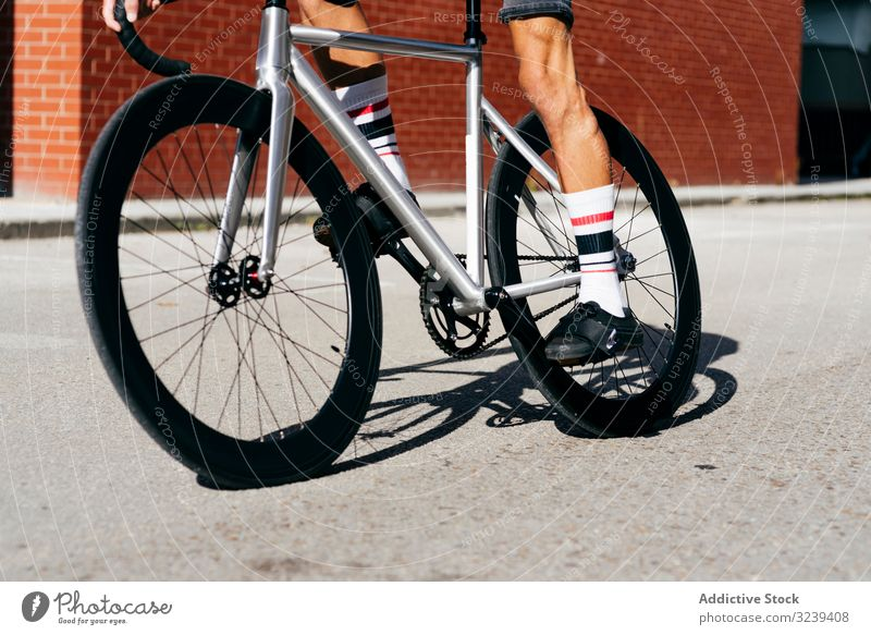 Sportive man riding a bike next to brick wall bicycle ride modern sportive active summer male handsome cyclist athletic recreation healthy equipment extreme