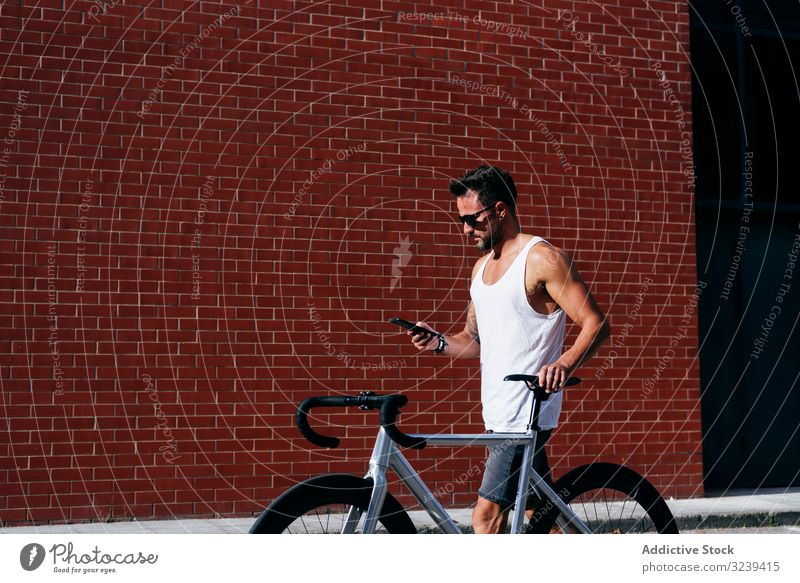 Sportive man with bicycle using phone bike stand mobile phone modern sportive active summer male sunglasses cyclist smartphone message texting checking reading