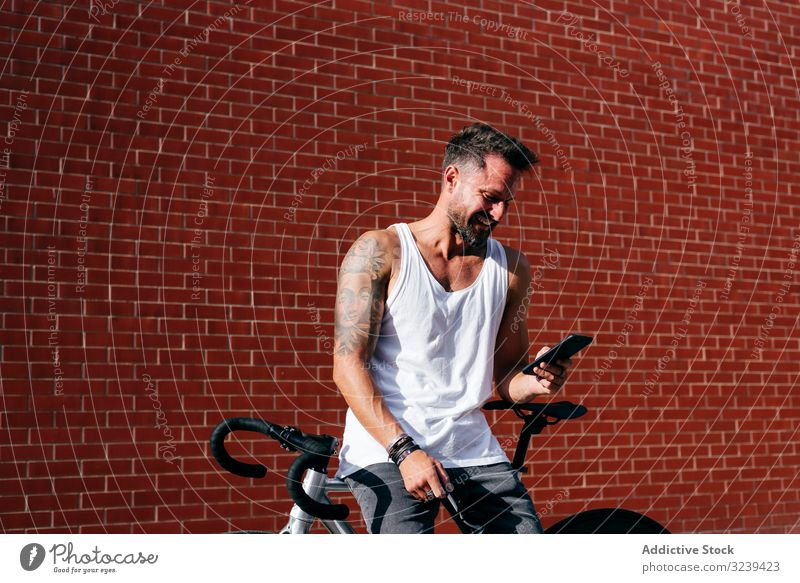 Sportive man with bicycle using phone bike stand mobile phone modern sportive active summer male cyclist smartphone message texting checking reading direction