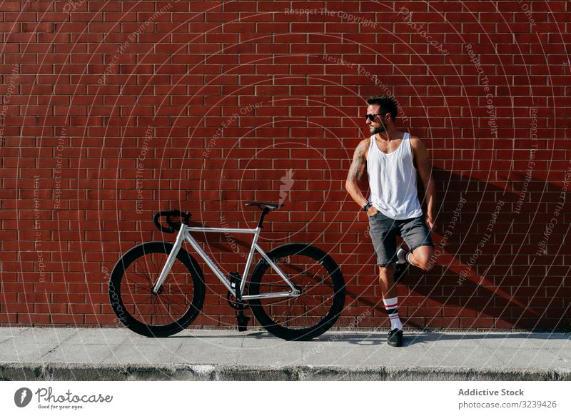 Sportive man standing next to brick wall with bike bicycle rest modern sportive active leaning relax summer male handsome confident sunglasses cyclist athletic