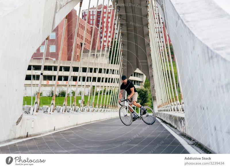 Man riding a bicycle on footbridge man bike city ride modern active sportive summer male adult cap cyclist healthy adventure leisure equipment track travel town