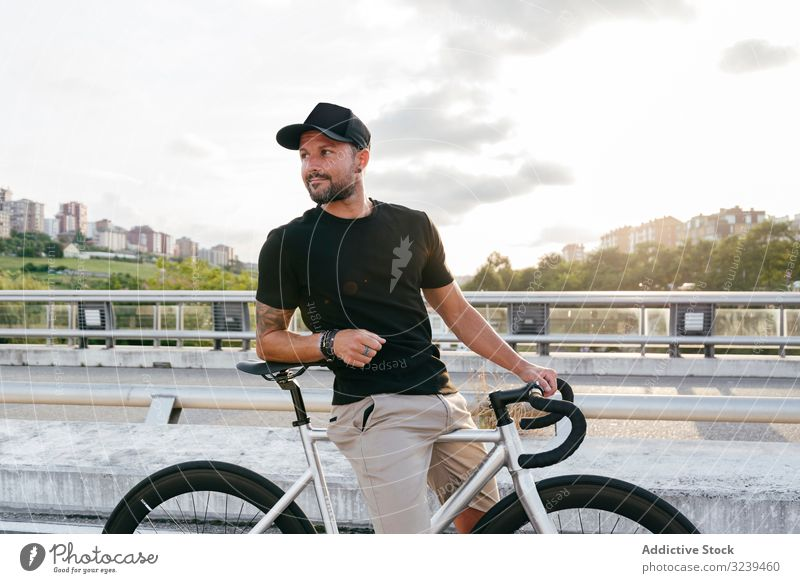 Cheerful man with bicycle standing on footbridge bike city ride modern active sportive summer male adult happy cheerful smile beard cap cyclist recreation