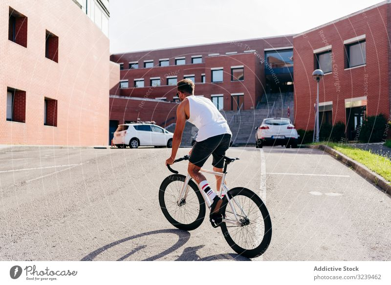 Man riding bike next to buildings man ride bridge city modern active sportive bicycle summer male sunglasses cyclist recreation healthy adventure equipment