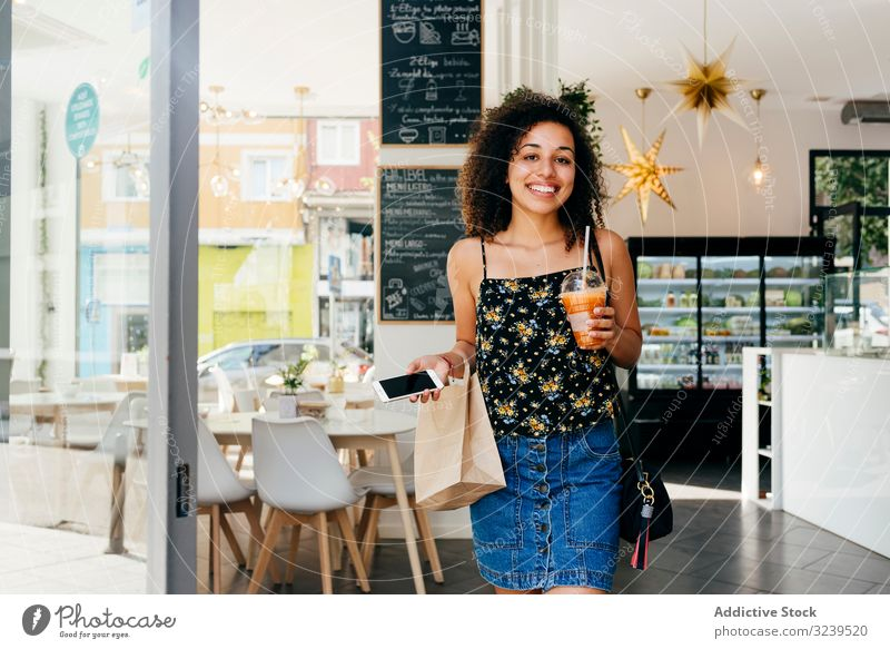 Cheerful ethnic woman leaving restaurant cafe drink healthy smile smartphone paper bag leave female urban vitamin beverage juice smoothie cup detox cheerful