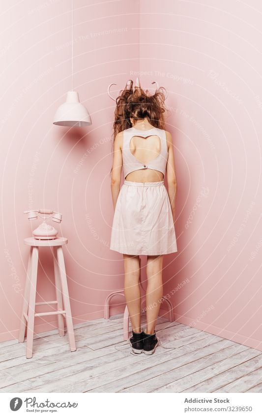 Back view of a young girl telephone wall lamp indoor pink unsatisfied long hair angry passive standing unhappy hair style loss stress haircare bad looking lady