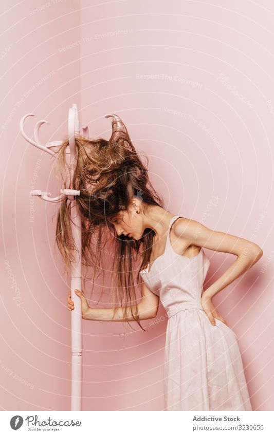 Teen girl with tangled hairs clothes rack indoor pink annoyed girl frustrated female angry woman single difficulties nervous damaged desperate expressive casual