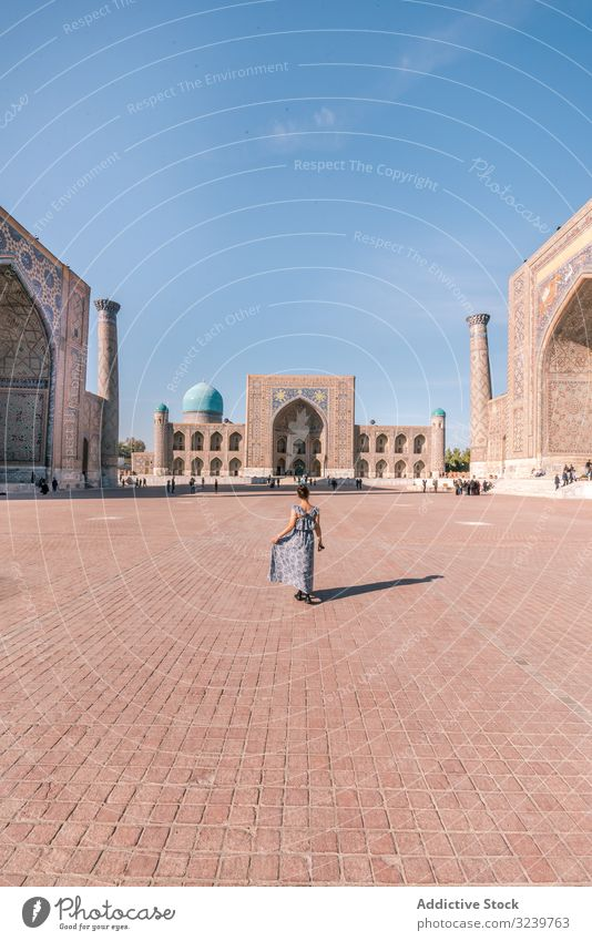 Unrecognizable female traveler walking on square tourist building traditional islamic ornament woman registan samarkand uzbekistan paved architecture oriental